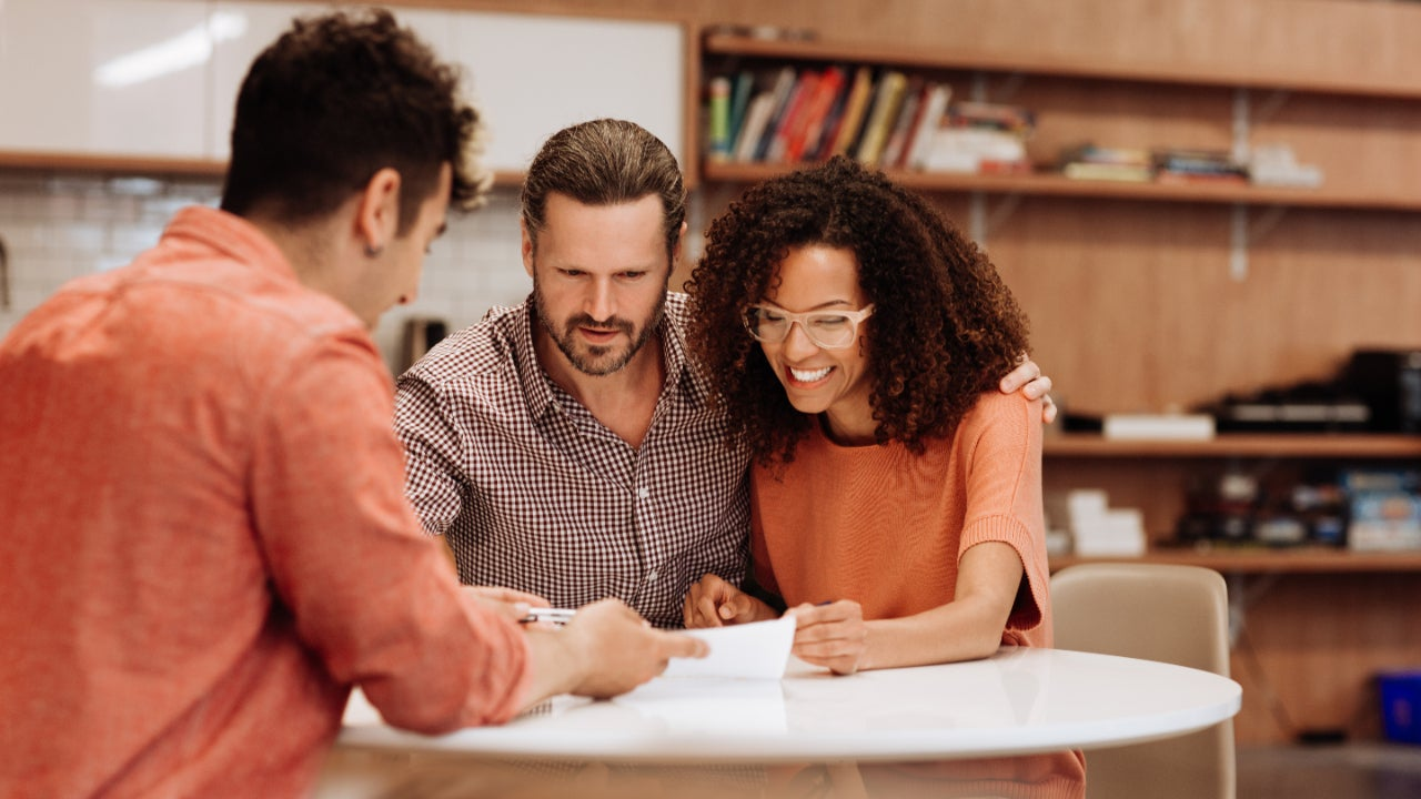 Young couple review paperwork, she looks happy and he looks mildly concerned
