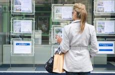 Hispanic woman looking at real estate window ads
