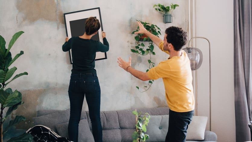 Two homeowners hang a photo