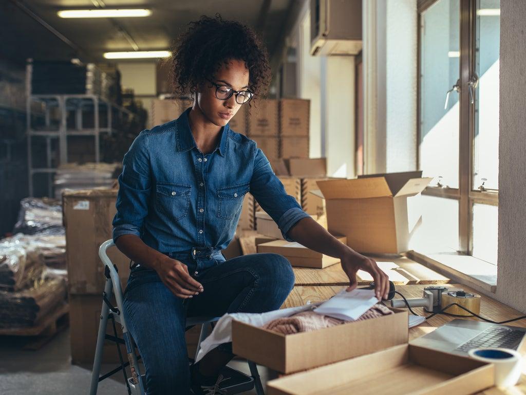 Female entrepreneur packaging box for delivery.