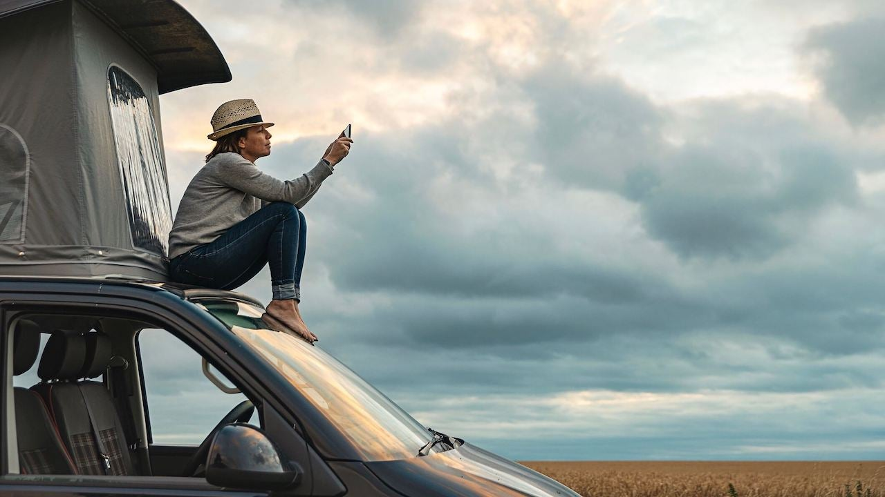 Woman taking a photo whilst sitting on roof of camper at sunset