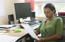 African businesswoman reading paperwork at desk