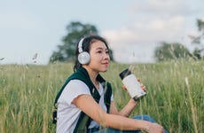 Young Woman Relaxing In Nature, Drinking With A Reusable Coffee Cup