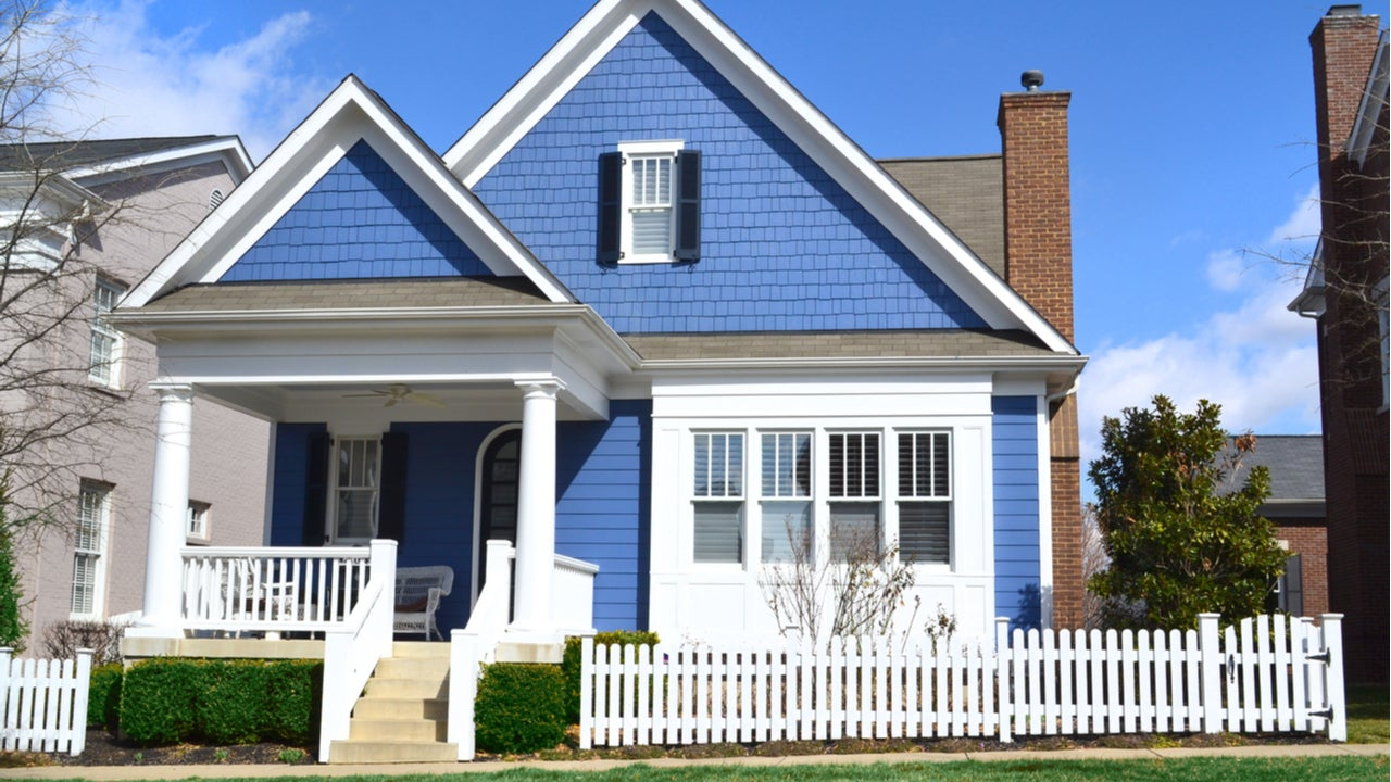 A blue single-family home with picket fence