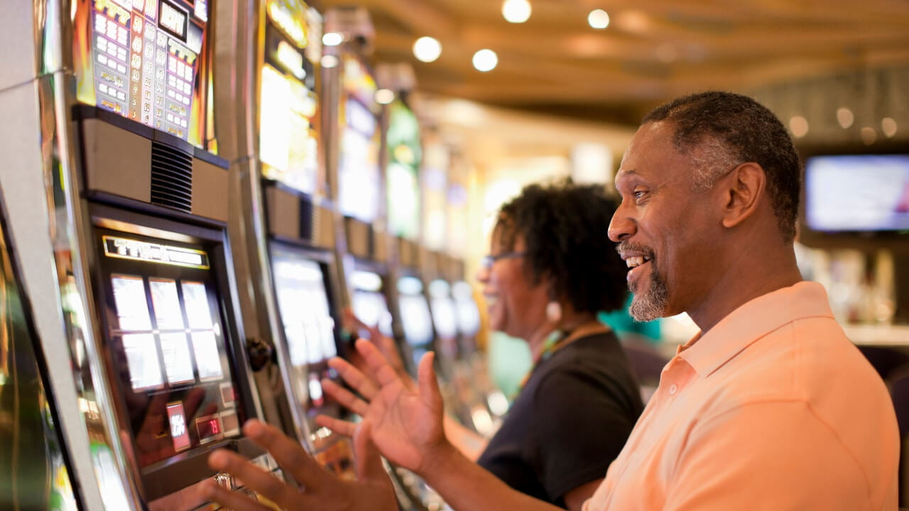 Couple playing slot machines at a casino