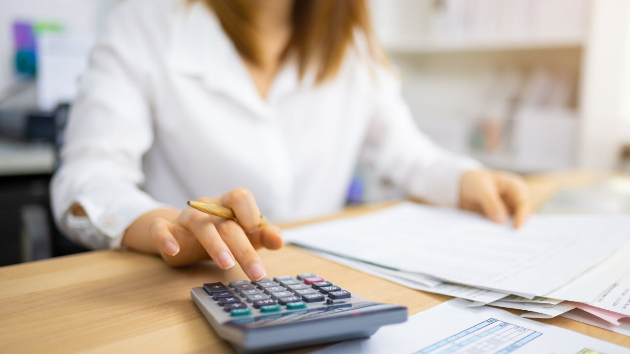 Woman using a calculator and examining financial documents
