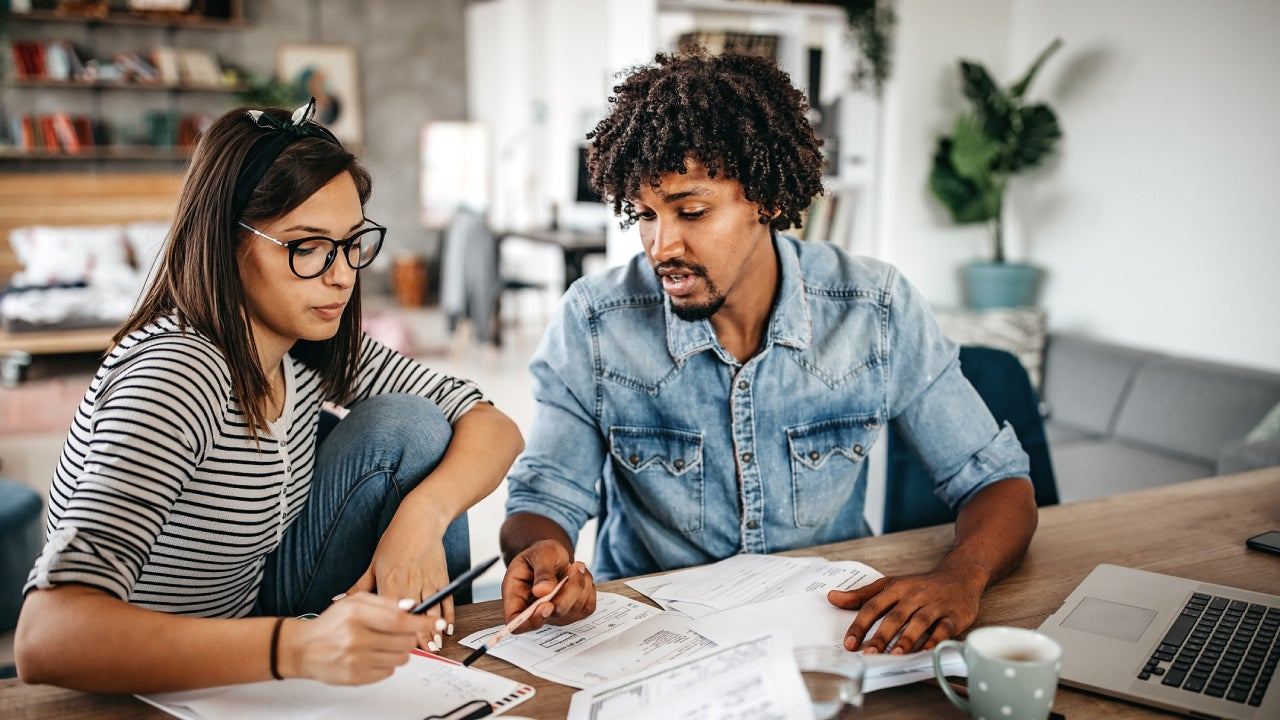 Multi-ethnic couple planning their home budget