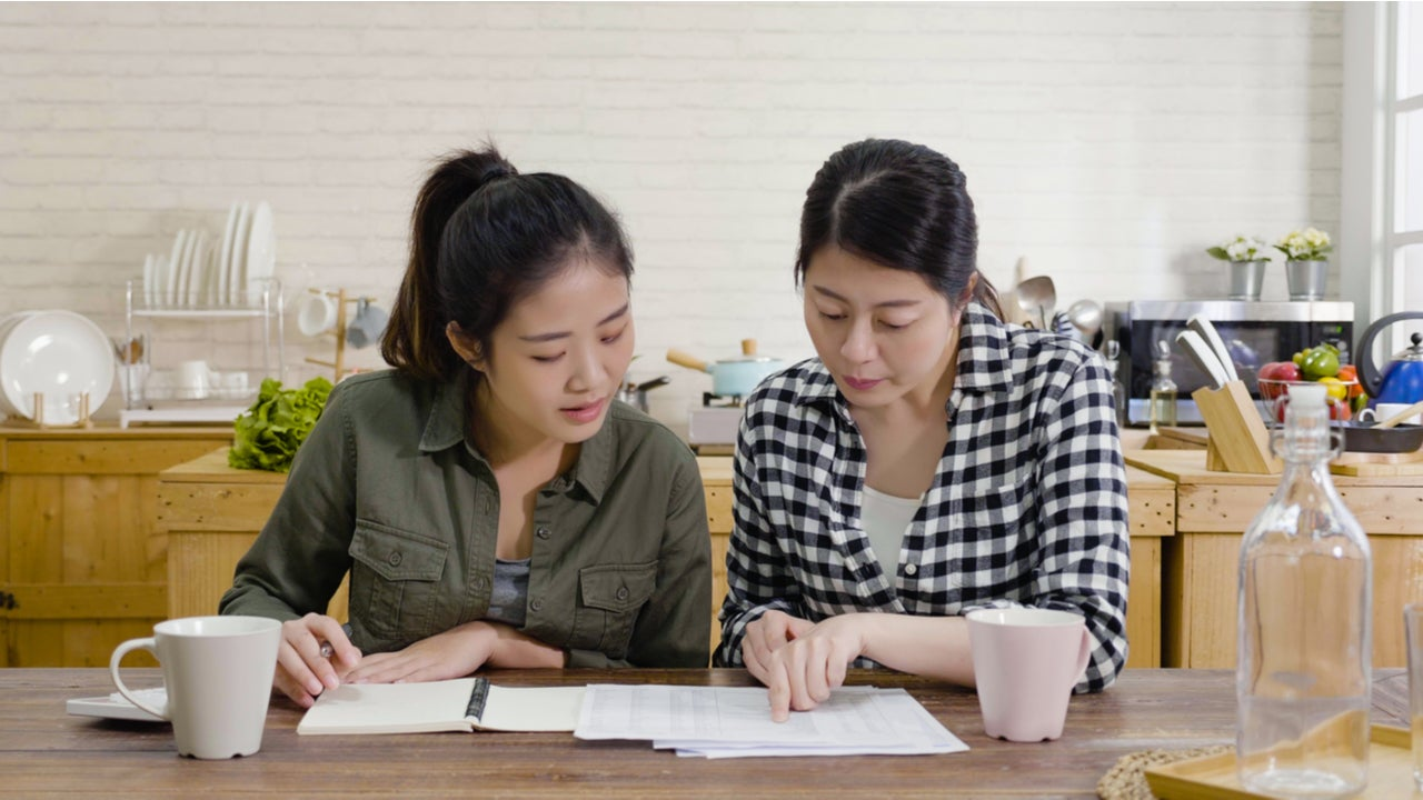 Two women go over paperwork in the kitchen
