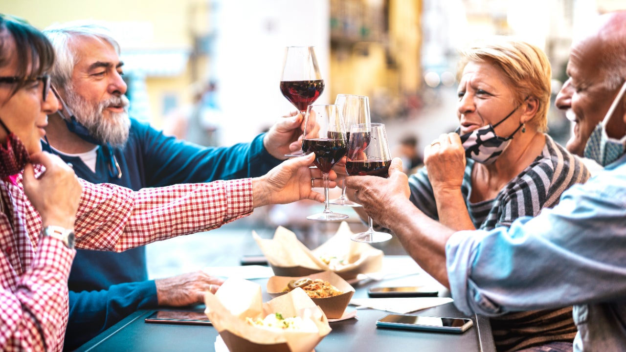 Four people clinking their wine glasses together at a dining table.