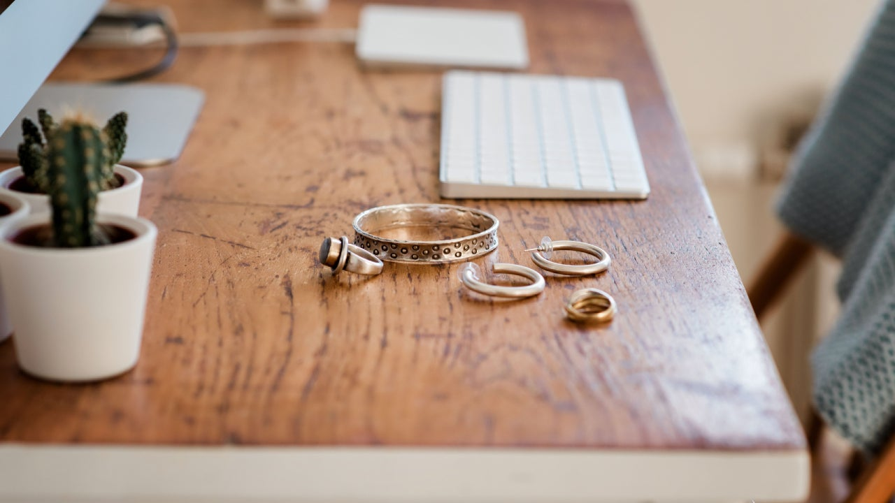 Woman's silver jewellery on a desk next to a computer