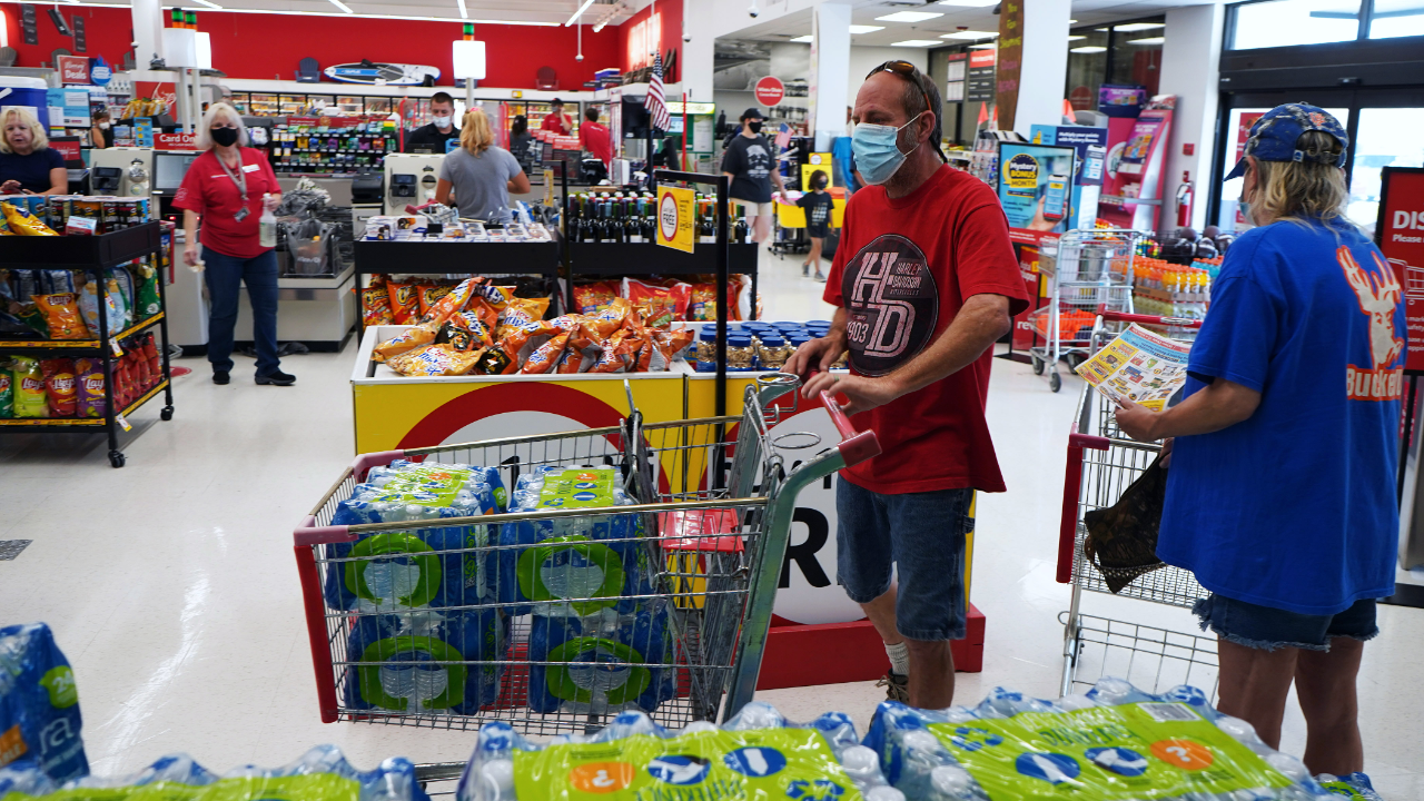 A shopper wearing a protective face mask fills a grocery cart with bottled water at a supermarket.