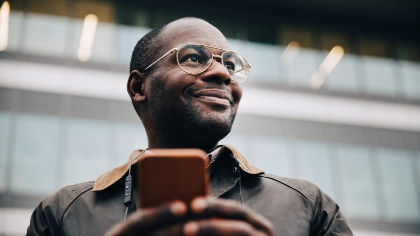 A businessman with a phone smiles and looks into the distance