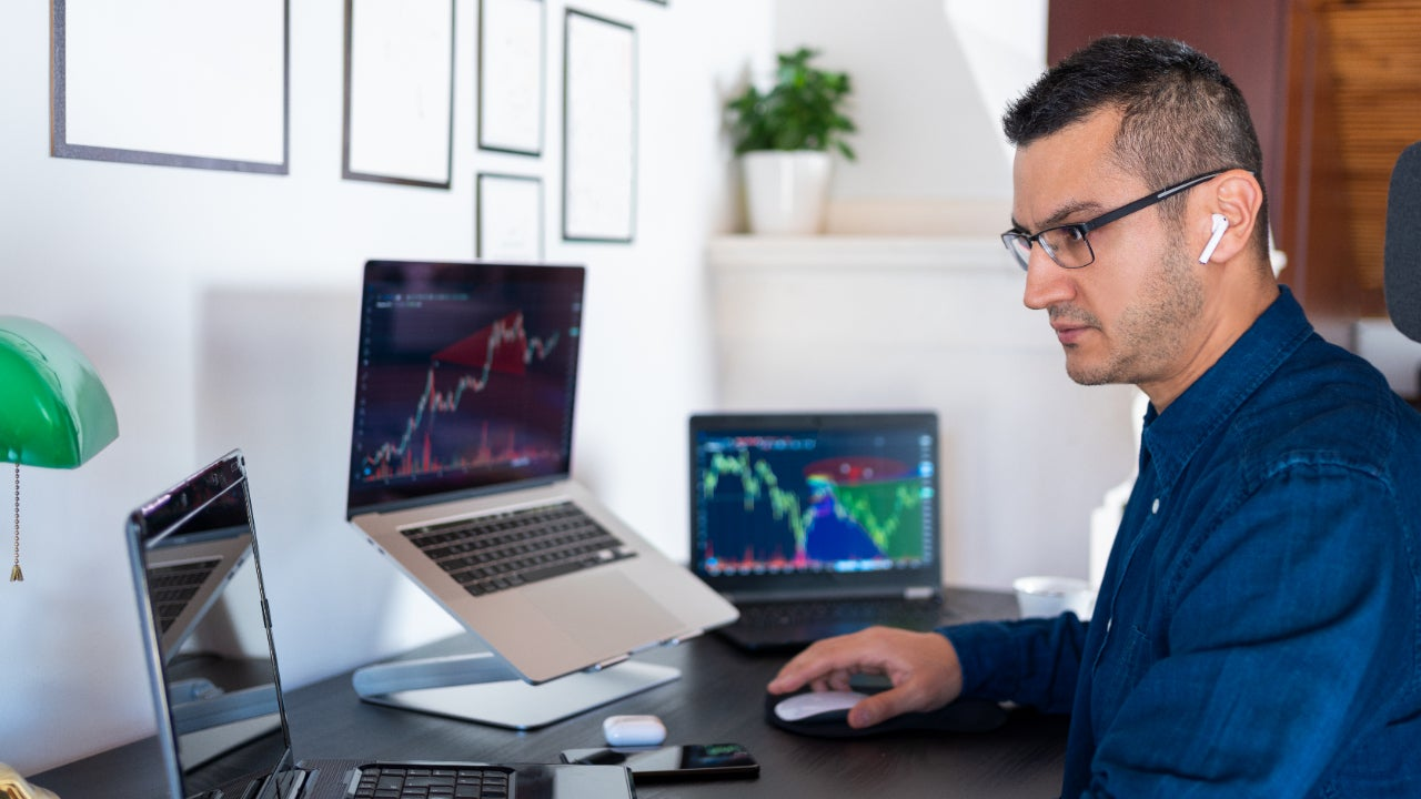 Man sitting at desk with headphones in looking at charts on three laptops