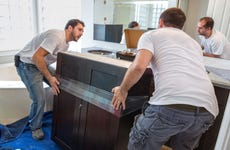 Two men install a new bathroom cabinet