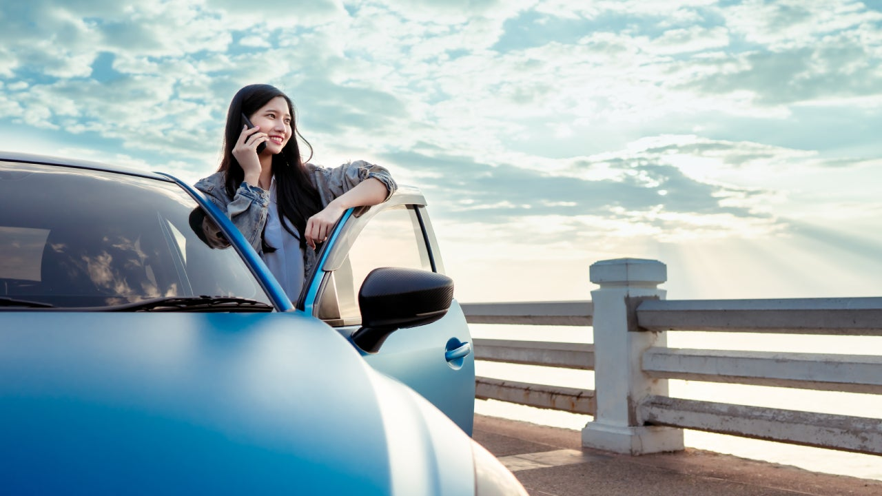 Beautiful teenager asian woman with car travel blue hatchback at beach using smartphone technology enjoy the view happy road trip driving, Freedom people lifestyle in holidays weekend