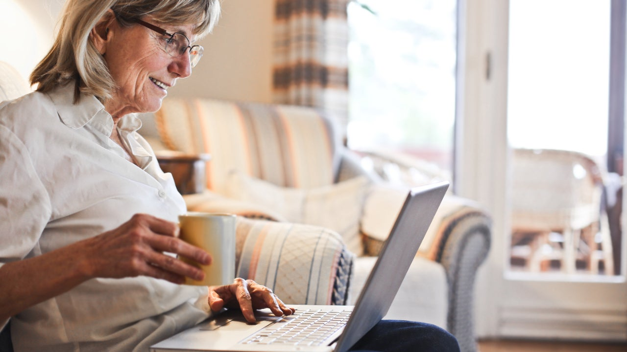 Older woman looking at laptop and holding cup