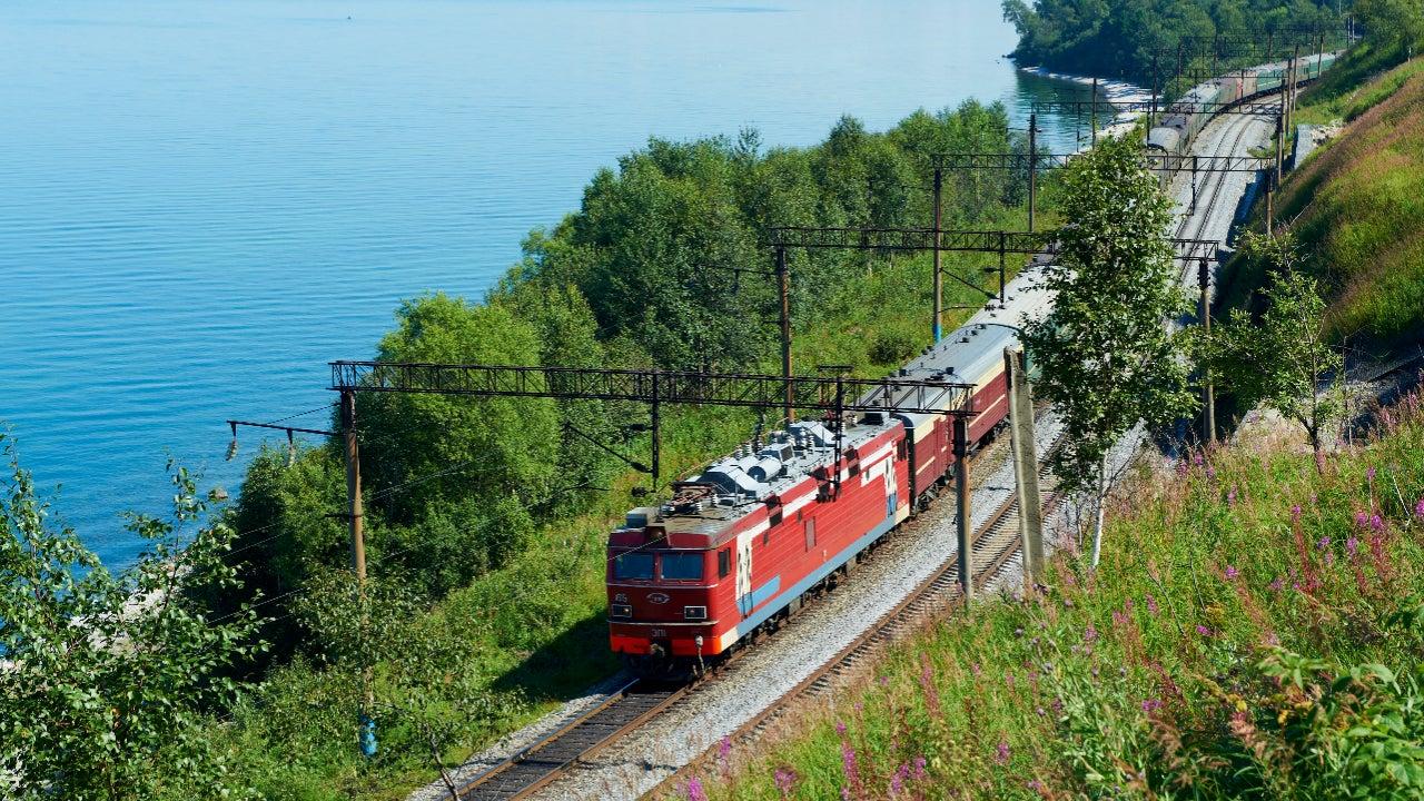 Trans-Siberian train traveling alongside large lake on sunny day