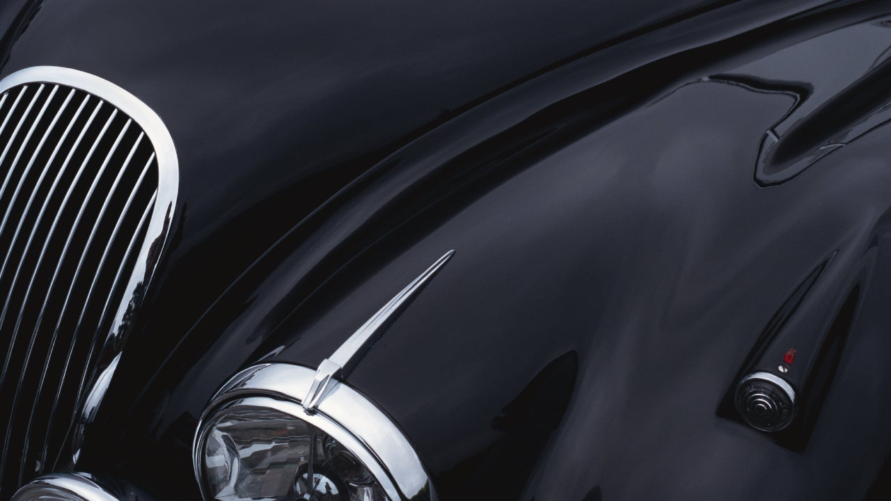 a black jaguar sports car hood showing a grill and headlight