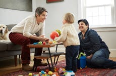 Lesbian moms play with their daughter in living room