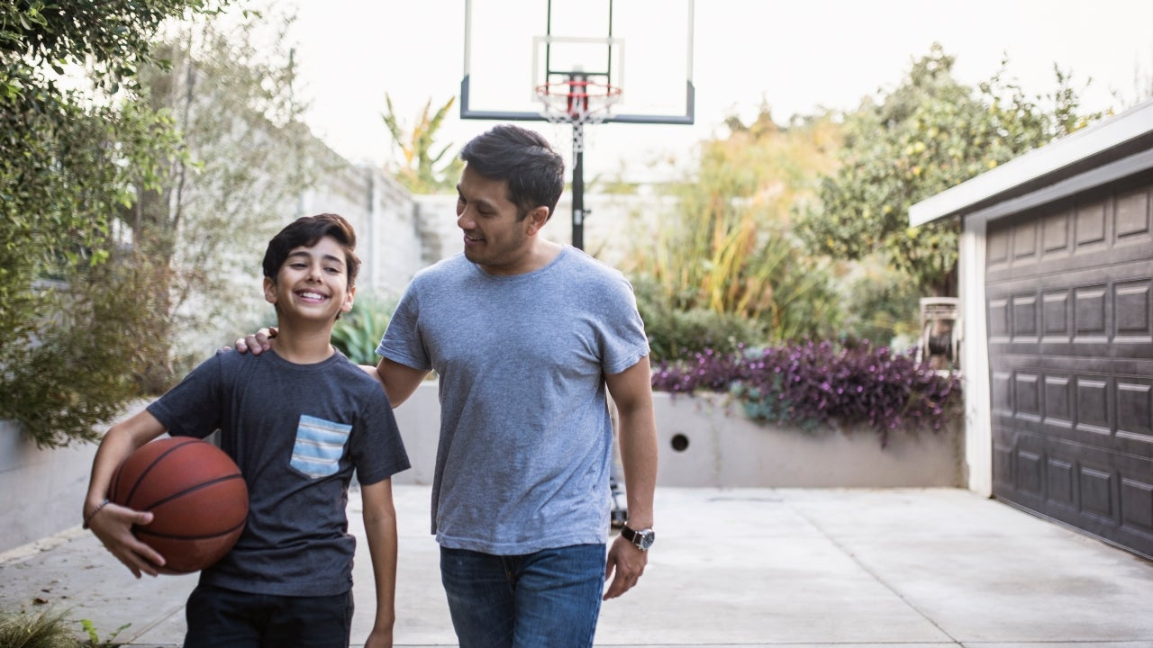 A father and son walk back inside after playing basketball in the driveway at their home