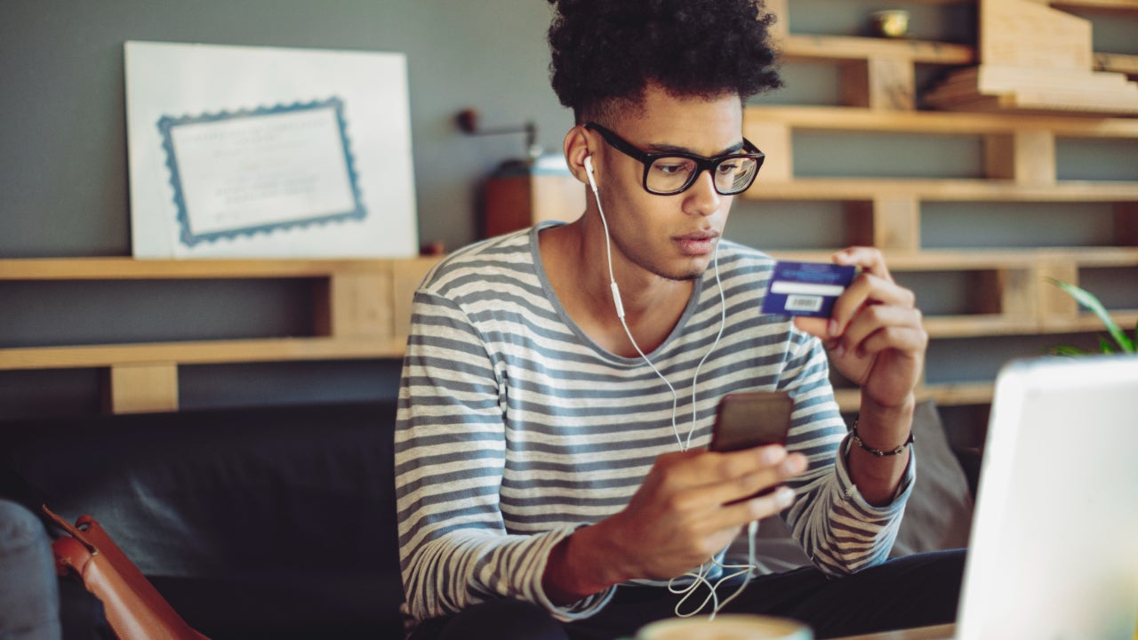 Young person with laptop and credit card.