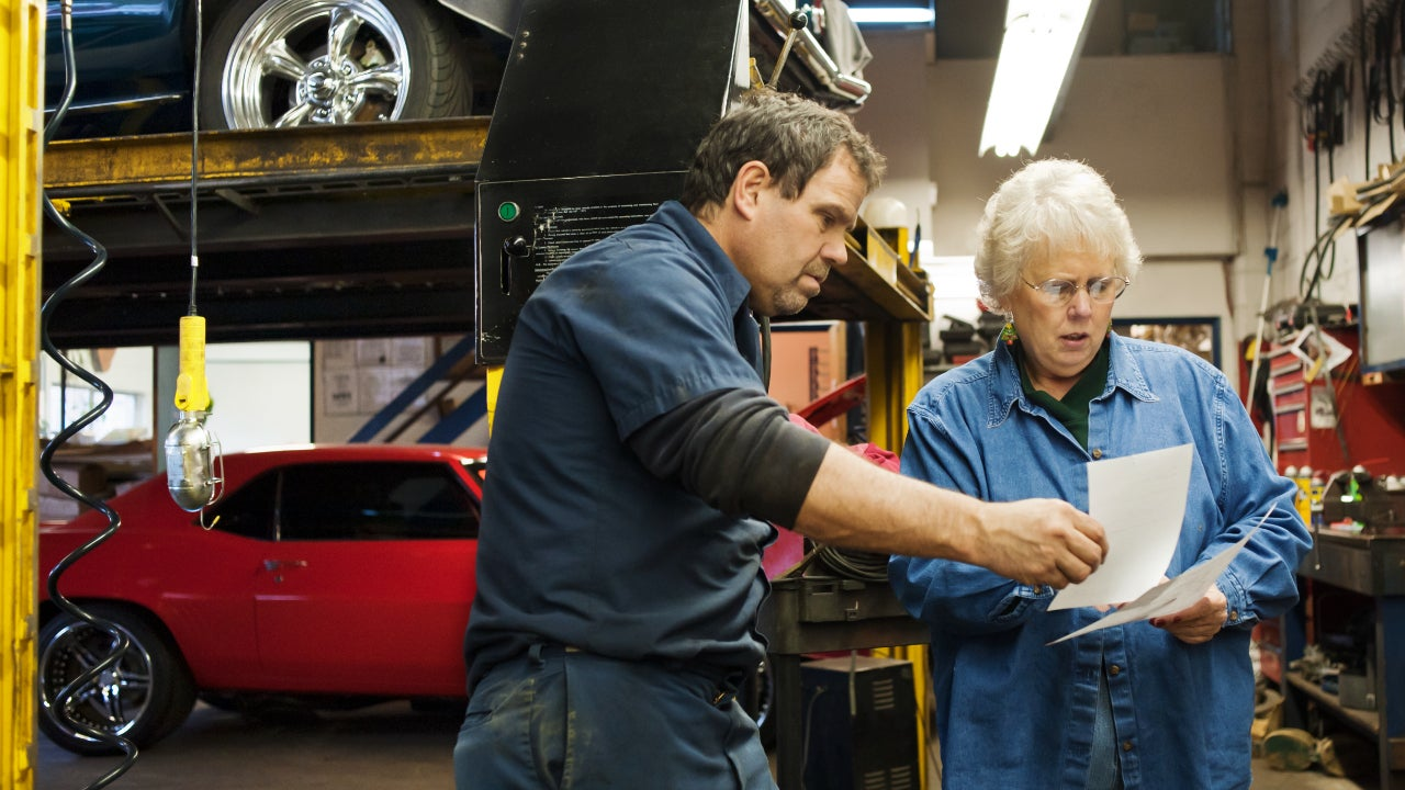 A mechanic discusses a bill with a customer