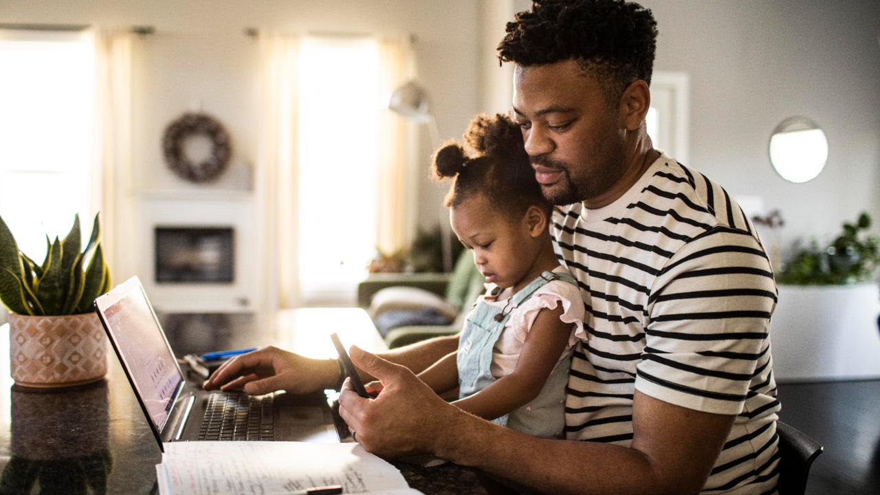 Man with baby at computer.