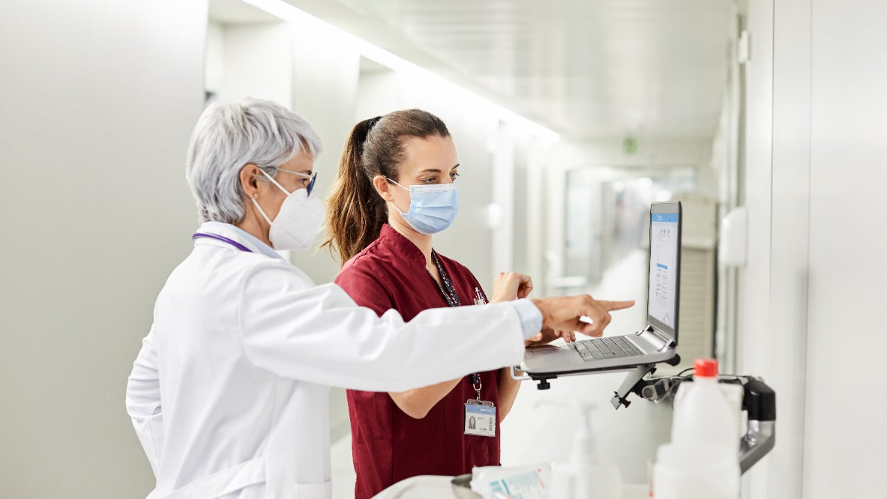 A doctor and nurse consult in front of a computer