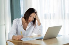 Worried young woman with laptop working from home looking at documents