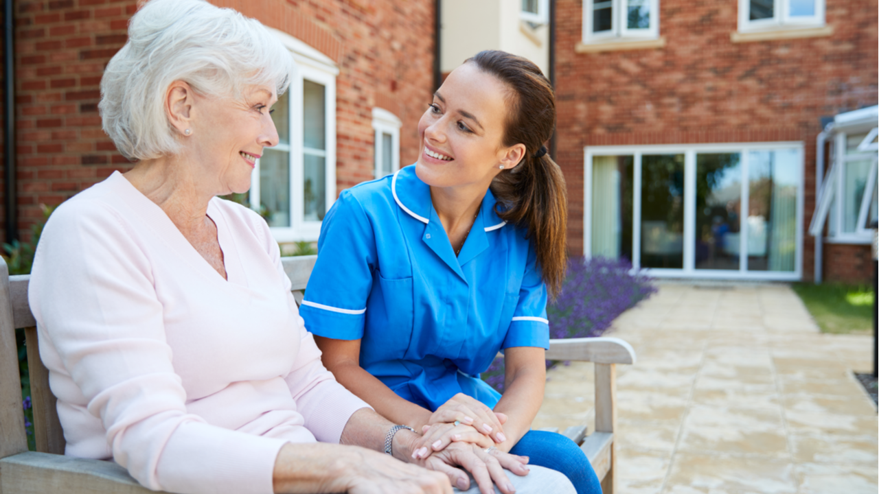 Nurse talks with a woman in a retirement home