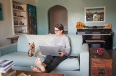 A woman with a laptop sits on a couch with a small dog
