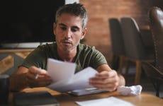 A worried man looks through bills
