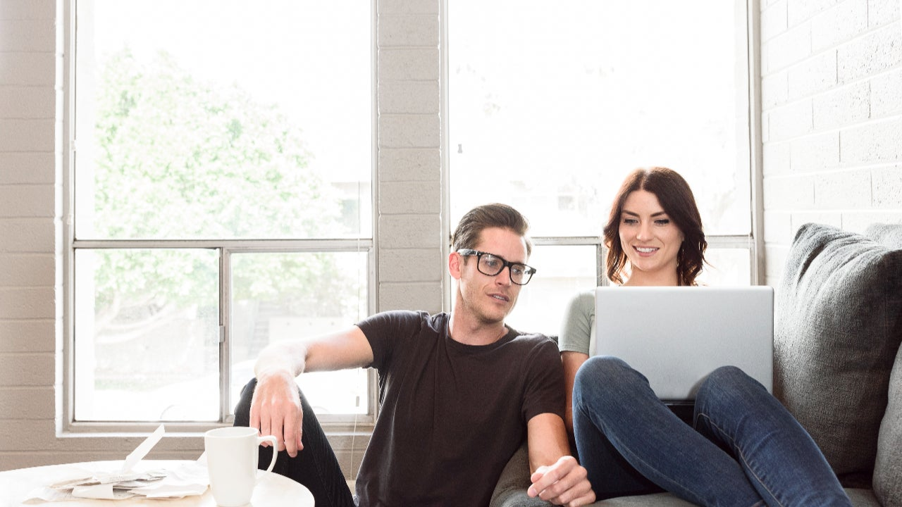 A young couple sits on a couch with their laptop