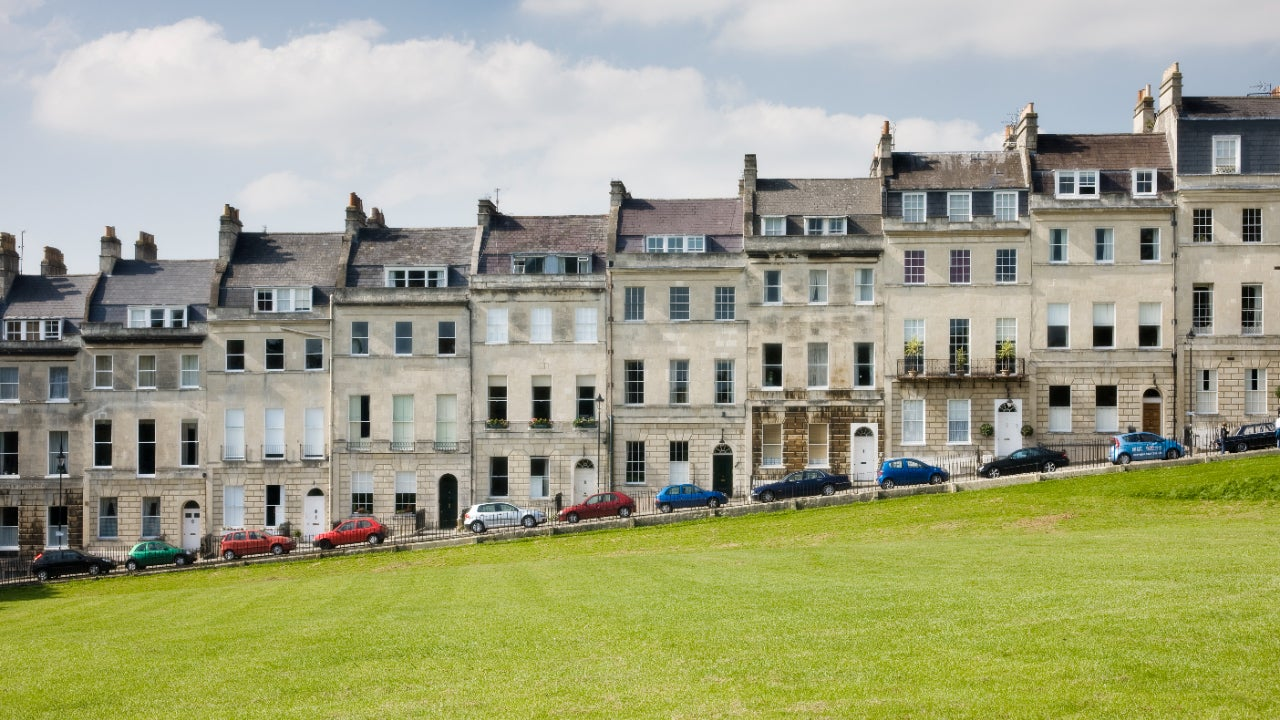 Cars parked outside Georgian terraced town houses that form the Royal Crescent in the city of Bath, Somerset