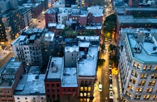 Overhead view of the busy streets of Nolita and SoHo neighborhoods with colorful night lights shining at dusk in Manhattan, New York City NYC