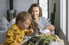 A mother and her toddler son planting an indoor garden during the COVID home quarantine.