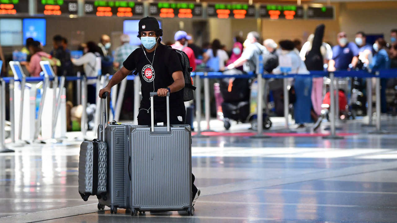 A man pushes his bags on the departures level at Los Angeles International Airport while wearing a mask.
