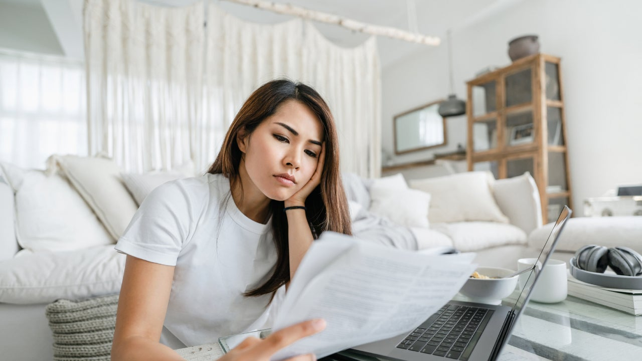Stressed and worried young Asian woman working from home, handling paperworks and going through her financials