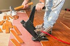 A carpenter lays hardwood flooring