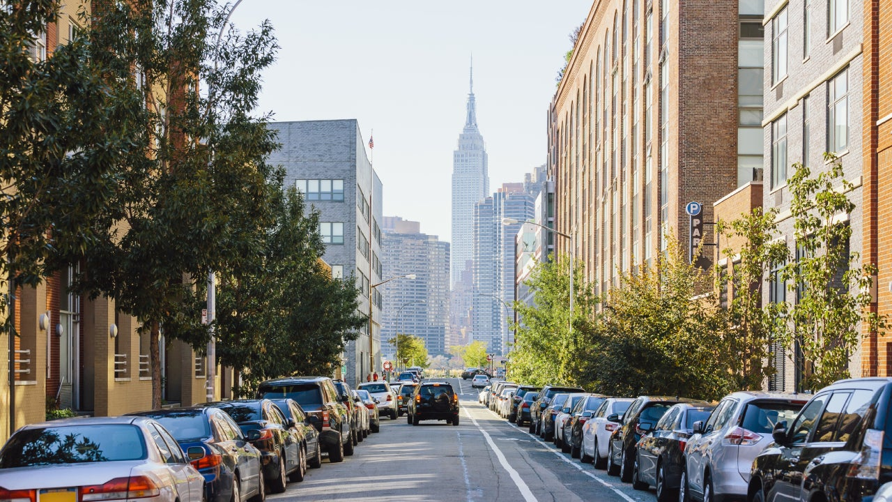 Street in Queens and Empire State Building in the center, New York City, USA