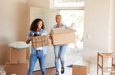 Lesbians Carrying Boxes Into New Home On Moving Day