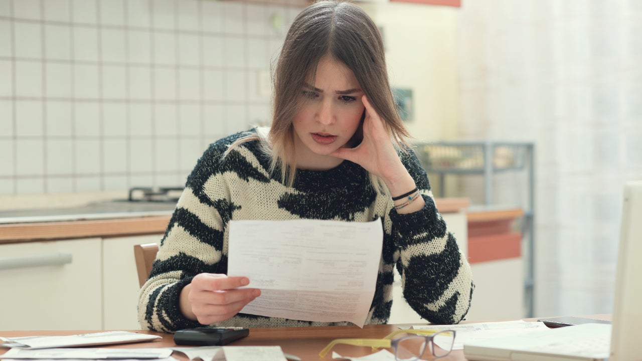 A worried woman looks at bills