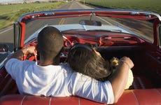 Hispanic couple driving in convertible
