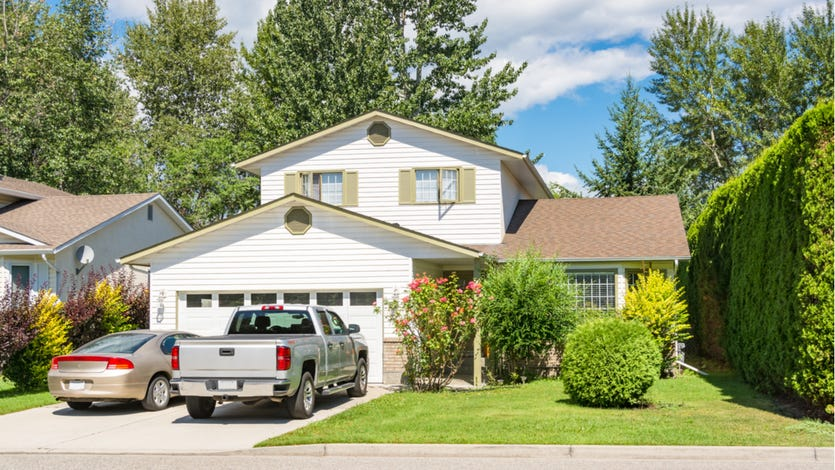 A single-family home with attached garage and two cars in the driveway