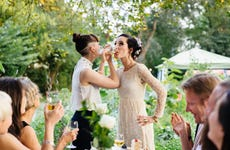 Newlywed lesbian couple drink champagne at reception with friends