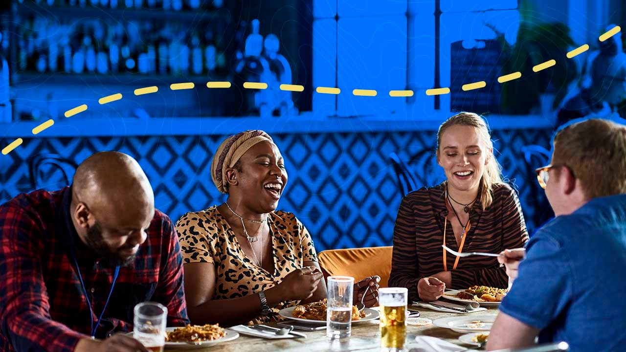 Friends laugh while gathered at a table eating a meal and socialization.