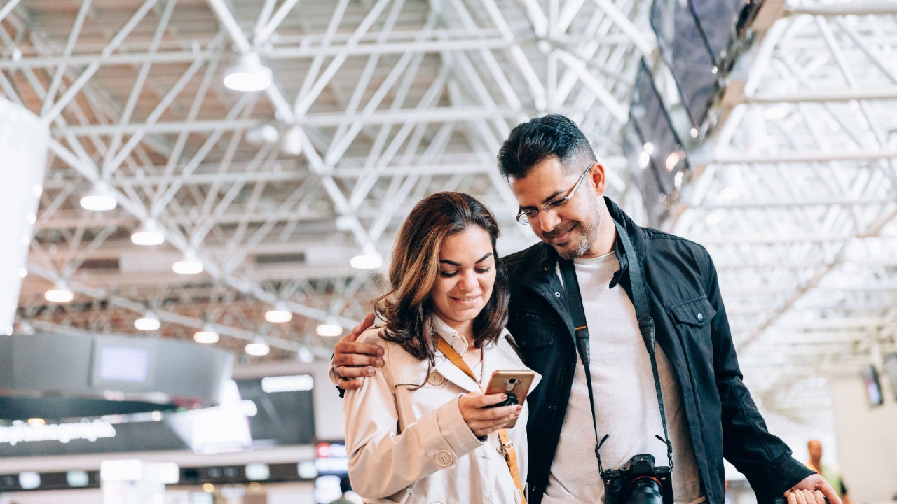 Couple at airport looking at smartphone