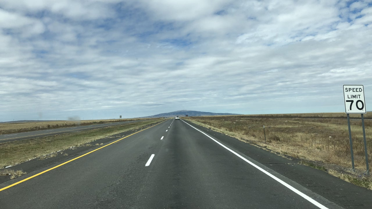 A highway with no one on it and a speed sign.