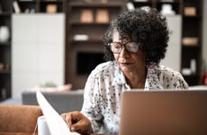 Senior woman working from home or using laptop planning or paying bills