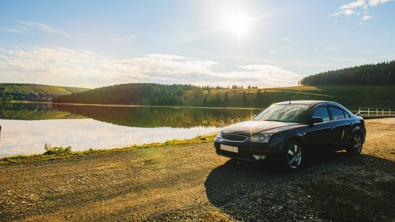 Car parked by lake on rolling landscape